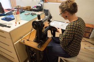 Bernadette Hartl näht auf der 100 Jahre alten Singer Schusternähmaschine mit Fußantrieb