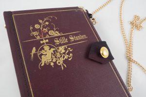 """Tasche aus dem weinroten Buch """"Stille Stunden"""" mit schönen Goldprägungen am Cover"""