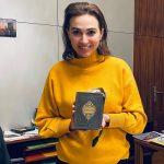 """Alma Zadic, Justizministerin von Österreich seit Jänner 2020 mit einer Bernanderl Tasche """"Novellen"""", das aus dem Buch eines ehemaligen Justizministers gefertigt ist."""