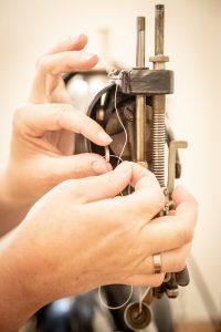 Einfädeln bei der 100 Jahre alten Singer-Nähmaschine mit Fußantrieb