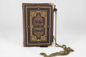 """Tasche/Clutch aus einem Buch """"The Rose, Thiele and Shamrock"""" in braun mit Gold- und Schwarzprägungen kombiniert mit einer ähnlich gemusterten Krawatte"""