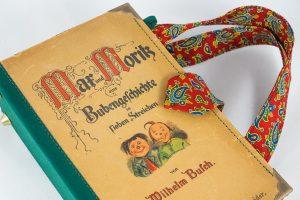 Tasche aus einem Max und Moritz Buch von Wilhelm Busch, kombiniert mit einer rot/grün/blauen Paisley-Krawatte und grünem Stoff