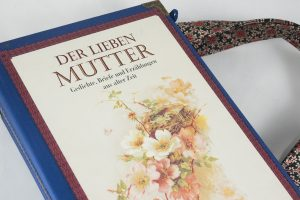 """Tasche aus dem Buch """"Der lieben Mutter"""" in blau kombiniert mit einer rosa-blumigen Krawatte, wie Blumen am Cover"""